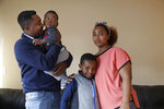 In this photo taken Sept. 24, 2019, Yonas Yeshanew, left, who resigned as Ethiopian Airline's chief engineer this summer and is seeking asylum in the U.S., poses with his family, including wife Tigist Hailu and sons Nathan Yonas, 1, and Yoel Yonas, 5, in Seattle area. Yeshanew says in a whistleblower complaint filed with regulators that the carrier went into the maintenance records on a Boeing 737 Max jet a day after it crashed this year, a breach he contends was part of a pattern of corruption that included fabricating documents, signing off on shoddy repairs and even beating those who got out of line. (AP Photo/Elaine Thompson)