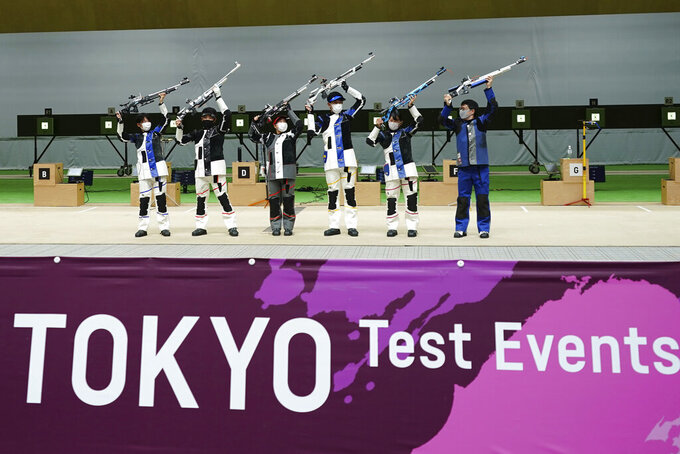 FILE - In this May 18, 2021, file photo, winning athletes pose after the finals of the 10m Air Rifle Mixed Team competition during the Tokyo 2020 Olympic Game Shooting test event at Asaka Shooting Range in Tokyo. IOC officials say the Tokyo Olympics will open on July 23 and almost nothing now can stop the games from going forward.(AP Photo/Eugene Hoshiko, File)