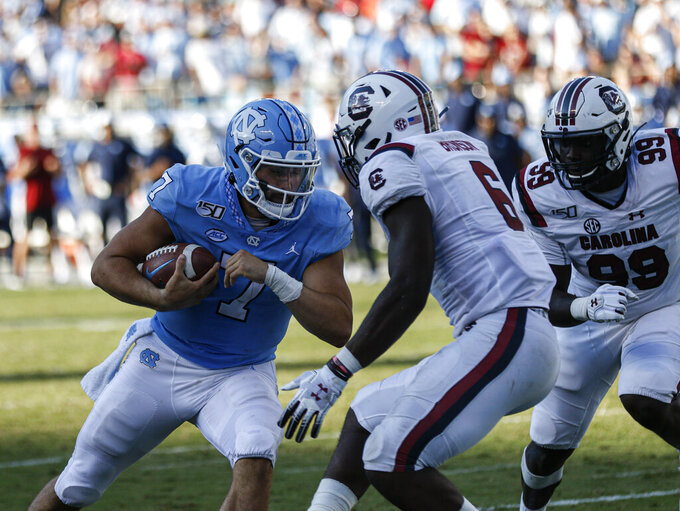 North Carolina quarterback Sam Howell (7) scores a two-point conversion against South Carolina linebacker T.J. Brunson (6) and defensive lineman Jabari Ellis (99 in the second half of an NCAA college football game in Charlotte, N.C., Saturday, Aug. 31, 2019. North Carolina won 24-20. (AP Photo/Nell Redmond)
