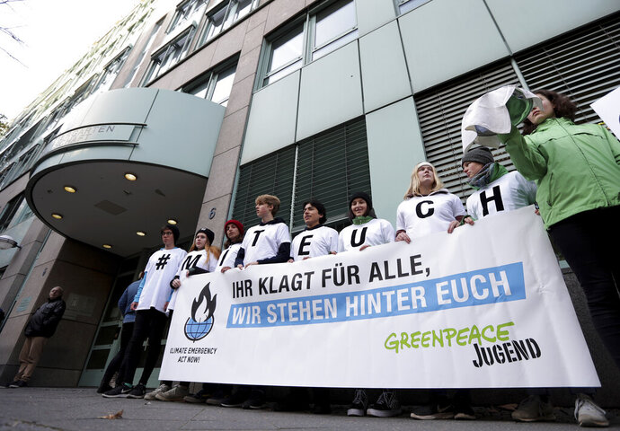 Activists of the environment protection organisation 'Greenpeace' take part in a protest rally in front of the administrative court in Berlin, Germany, Thursday, Oct. 31, 2019. Three German farming families are taking Chancellor Angela Merkel to court, arguing that her government isn't doing enough to tackle climate change. The lawsuit that will be heard Thursday is the first attempt in Germany to hold authorities legally accountable for pledges they have made to reduce greenhouse gas emissions. Slogan reads: 'You are sueing for everybody - we stay next to you'. (AP Photo/Michael Sohn)