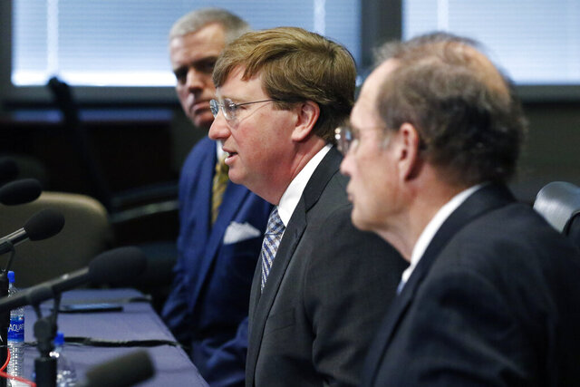 Gov. Tate Reeves, center, speaks of how he and House Speaker Philip Gunn, R-Clinton, left, and fellow Republican Lt. Gov. Delbert Hosemann, right, are now working on a deal about how to spend $1.2 billion in CARES Act funds, during Reeves' daily news conference, Thursday, May 7, 2020, in Jackson, Miss. Last Friday, the Legislature passed a bill that striped Reeves of sole spending authority. (AP Photo/Rogelio V. Solis)