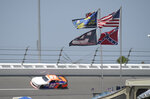 FILE - In this July 4, 2015, file photo, U.S., Confederate and Dale Earnhardt Sr. and Jr. flags fly near Turn 4 during NASCAR qualifying at Daytona International Speedway in Daytona Beach, Fla. NASCAR banned the Confederate flag from its races and venues Wednesday, June 10, 2020, formally severing itself from what for many is a symbol of slavery and racism. (AP Photo/Phelan M. Ebenhack, File)