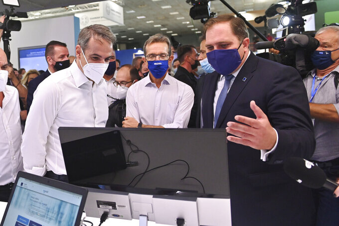 Greece's Prime Minister Kyriakos Mitsotakis, left, reacts as he looks at a computer monitor during a tour of Thessaloniki International Trade Fair, in the northern Greek city of Thessaloniki, Saturday, Sept. 11, 2021. The keynote speech Mitsotakis is set to deliver later Saturday is still under wraps, but aides have let it be known that it will focus on youth and small business owners. (AP Photo/Giannis Papanikos)