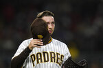 San Diego Padres starting pitcher Blake Snell takes off his cap for inspection during the first inning of a baseball game against the Los Angeles Angels, Tuesday, Sept. 7, 2021, in San Diego. (AP Photo/Gregory Bull)