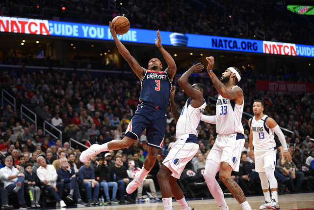 Washington Wizards guard Bradley Beal (3) goes to the basket next to Dallas Mavericks center Willie Cauley-Stein (33), guard Tim Hardaway Jr., center, and guard Jalen Brunson (13) during the second half of an NBA basketball game, Friday, Feb. 7, 2020, in Washington. (AP Photo/Nick Wass)