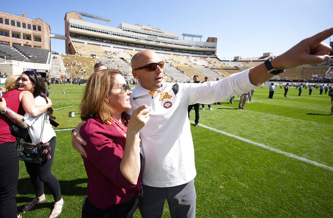 Minnesota head coach P.J. Fleck points to fans as he is congratulated after the second half of an NCAA college football game against Colorado, Saturday, Sept. 18, 2021, in Boulder, Colo. Minnesota won 30-0. (AP Photo/David Zalubowski)