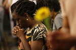 A woman clasps her hands in prayer during a memorial Mass to mark the one-year anniversary of the death of councilwoman Marielle Franco, at the Candelaria Catholic Church in Rio de Janeiro, Brazil, Thursday, March 14, 2019. Franco and her driver, Anderson Gomes, were gunned down in Central Rio, a brazen assassination that shocked Brazilians and sparked protests in several countries. (AP Photo/Silvia Izquierdo)