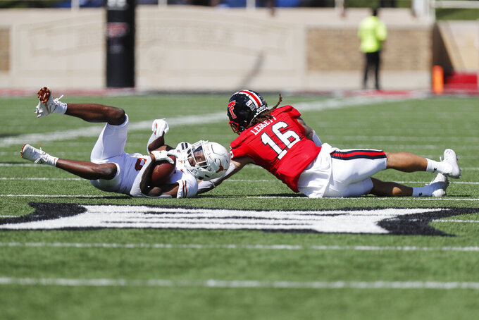 Texas wide receiver Joshua Moore is tackled after the catch by Texas Tech defensive back Thomas Leggett during the first half of an NCAA college football game against Texas Tech, Saturday Sept. 26, 2020, in Lubbock, Texas. (AP Photo/Mark Rogers)