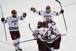 Massachusetts players gather around Zac Jones (24) after he scored against Minnesota Duluth during the first period of an NCAA men's Frozen Four hockey semifinal in Pittsburgh, Thursday, April 8, 2021. (AP Photo/Keith Srakocic)
