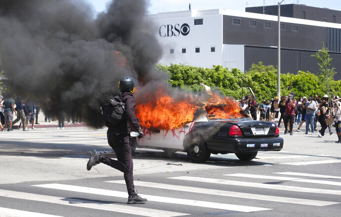 A person runs while a police vehicle is burning during a protest over the death of George Floyd in Los Angeles, Saturday, May 30, 2020. Protests across the country have escalated over the death of George Floyd who died after being restrained by Minneapolis police officers on Memorial Day, May 25. (AP Photo/Ringo H.W. Chiu)