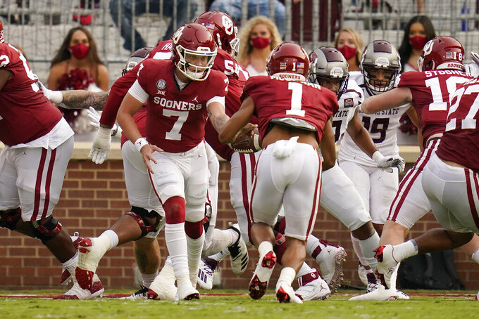 Oklahoma quarterback Spencer Rattler (7) hands off to Seth McGowan (1) who takes the ball in for a touchdown during an NCAA college football game against Missouri State Saturday, Sept. 12, 2020, in Norman, Okla. (AP Photo/Sue Ogrocki, Pool)