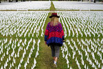FILE - In this Oct. 27, 2020, Artist Suzanne Brennan Firstenberg walks among thousands of white flags planted in remembrance of Americans who have died of COVID-19 near Robert F. Kennedy Memorial Stadium in Washington. The U.S. death toll from the coronavirus has eclipsed 400,000 in the waning hours in office for President Donald Trump. (AP Photo/Patrick Semansky, File)