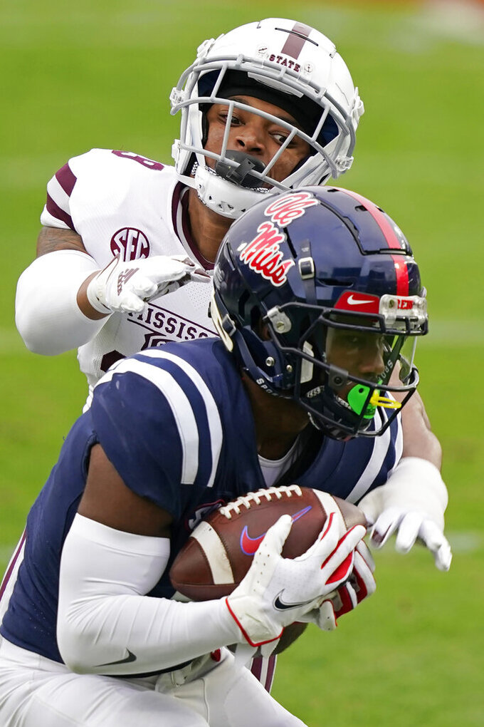 Mississippi wide receiver Elijah Moore (8) catches a pass in front of Mississippi State safety Collin Duncan during the first half of an NCAA college football game, Saturday, Nov. 28, 2020, in Oxford, Miss. Mississippi won 31-24. (AP Photo/Rogelio V. Solis)