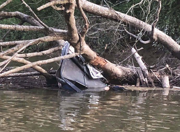 This photo provided by Louisiana Department of Wildlife and Fisheries Enforcement Division shows motorboat that crashed into a fallen tree on Thursday, Sept. 6, 2019 in Upper Amite River north of Bayou Manchac, La. The Department of Wildlife and Fisheries says a 23-year-old woman was injured in the wreck that killed  29-year-old Dustin Gore of St. Amant and 27-year-old Trent Kelly of Baton Rouge.  Agents found the men's bodies near the 16-foot aluminum boat.  (Louisiana Department of Wildlife and Fisheries Enforcement Division via AP)