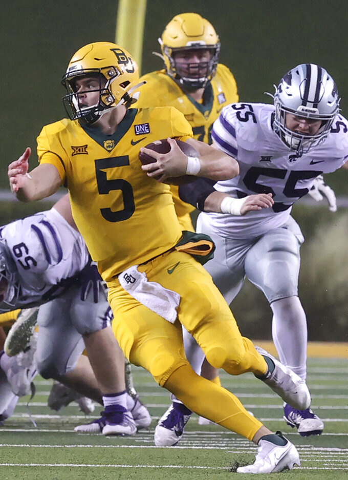 FILE - In this Nov. 28, 2020, file photo, Baylor quarterback Charlie Brewer, front, runs past Kansas State defenders for a first down in the first half of an NCAA college football game in Waco, Texas. Brewer will be quarterbacking the Utes after leaving Baylor. (Jerry Larson/Waco Tribune-Herald via AP, File)