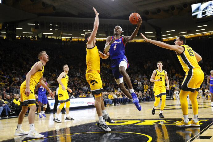DePaul forward Paul Reed (4) drives to the basket over Iowa center Luka Garza during the first half of an NCAA college basketball game, Monday, Nov. 11, 2019, in Iowa City, Iowa. DePaul won 93-78. (AP Photo/Charlie Neibergall)