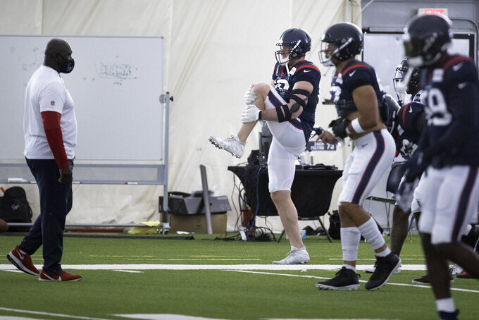 Houston Texans defensive end J.J. Watt (99) warms up with his teammates during an NFL training camp football practice Friday, Aug. 14, 2020, at The Houston Methodist Training Center in Houston. (Brett Coomer/Houston Chronicle via AP)
