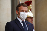 French President Emmanuel Macron, left, wearing a protective face mask, waits to welcome Armenian President Armen Sarkissian for a meeting at the Elysee Palace in Paris, Thursday, Oct. 22, 2020. (Charles Platiau/Pool via AP)
