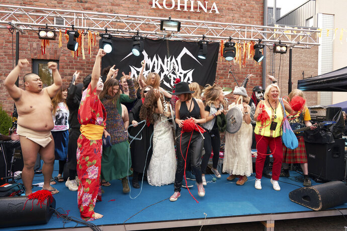 The competitors of the first Heavy Metal Knitting world championship react on stage, Thursday, July 11, 2019 in Joensuu, Finland. With stage names such as 'Woolfumes,' 'Bunny Bandit' and '9