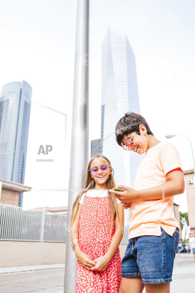 Boy using mobile phone while standing with friend in city