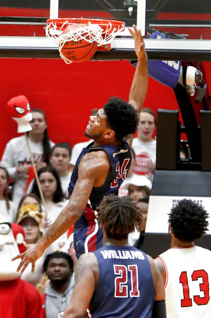 Fairleigh Dickinson's Mike Holloway Jr. (34) dunks past St. Francis Pa.'s Keith Braxton (13) during the first half of an NCAA college basketball game for the championship of the Northeast Conference men's tournament, Tuesday, March 12, 2019, in Pittsburgh. (AP Photo/Keith Srakocic)