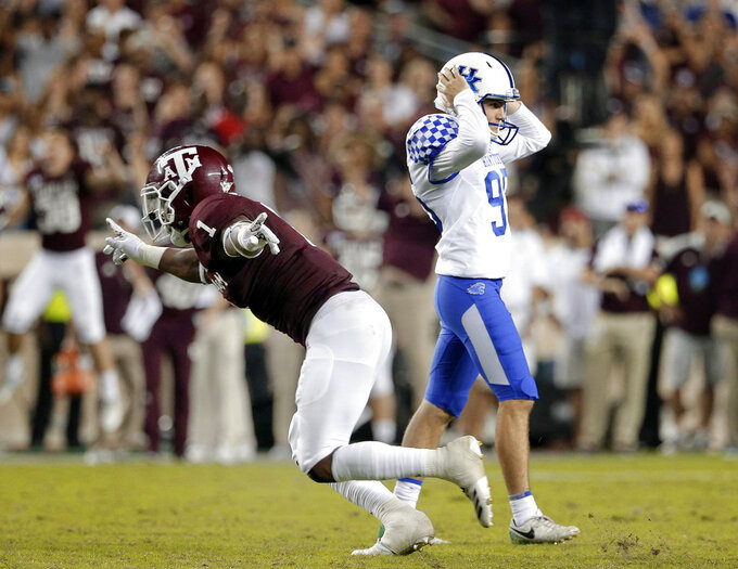 FILE - In this Saturday, Oct. 6, 2018, file photo, Texas A&M linebacker Buddy Johnson (1) runs off the field signaling no score as Kentucky place-kicker Miles Butler (95) reacts after missing a field goal in overtime of an NCAA college football game in College Station, Texas. A week ago, the SEC had four teams in the top eight: No. 1 Alabama, No. 2 Georgia, No. 5 LSU and No. 8 Auburn.  Instead, LSU, Auburn and Kentucky lost, allowing the three teams that beat them to either remain ranked or enter the AP Top 25.  (AP Photo/Michael Wyke, File)
