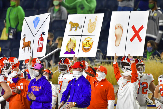 Clemson sideline personnel hold play signal cards during the third quarter of the team's NCAA college football game against Notre Dame on Saturday, Nov. 7, 2020, in South Bend, Ind. (Matt Cashore/Pool Photo via AP)