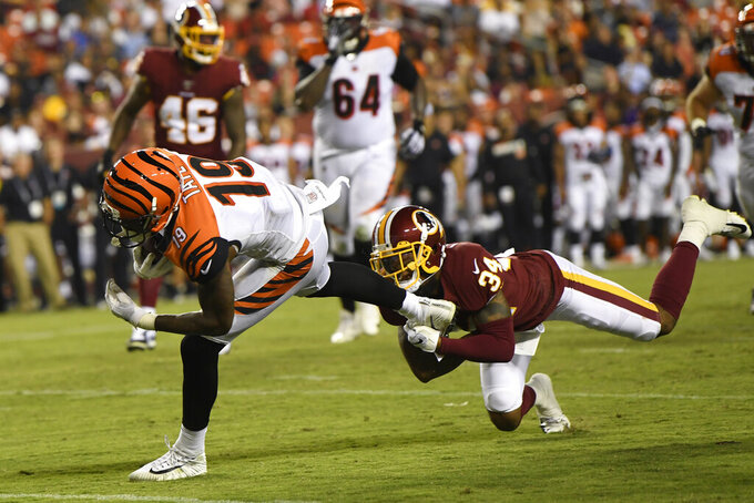 Washington Redskins cornerback Ashton Lampkin (34) holds on to the foot of Cincinnati Bengals wide receiver Auden Tate (19) during the third quarter of an NFL preseason football game in Landover, Md., Thursday, Aug. 15, 2019. The Bengals beat the Redskins, 23-13. (AP Photo/Susan Walsh)