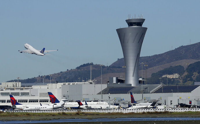 FILE - In this Oct. 24, 2107 file photo, the air traffic control tower is in sight as a plane takes off from San Francisco International Airport in San Francisco. Aviation-safety officials say a close call last year highlights the need for faster reporting of dangerous incidents before evidence is lost. The National Transportation Safety Board issued a final report Thursday, Oct. 11, 2018  on the July 2017 close call in which an Air Canada jet nearly crashed into planes lined up on the ground at San Francisco International Airport. (AP Photo/Jeff Chiu, File)