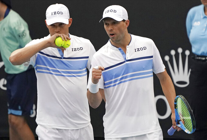 FILE - In this Jan. 22, 2020, file photo, Bob, left, and Mike Bryan talk during their first round doubles match against India's Rohan Bopanna and Japan's Yasutaka Uchiyama at the Australian Open tennis championship in Melbourne, Australia. Any World TeamTennis player or coach who tests positive for COVID-19 when arriving for the three-week 2020 season will be dropped from the league without pay. The health plan released Tuesday, June 16, 2020, by the WTT for its matches starting July 12 at The Greenbrier in West Virginia also calls for two daily temperature checks for spectators, no ball kids, a chair umpire aided by electronic line-calling instead of line judges, and no high-fives or handshakes between opponents. The rosters announced for the WTT's nine teams include Grand Slam title winners Kim Clijsters, Sloane Stephens, Sofia Kenin and the Bryan brothers. (AP Photo/Lee Jin-man, File)
