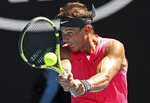 Spain's Rafael Nadal makes a backhand return to Bolivia's Hugo Dellien during their first round singles match at the Australian Open tennis championship in Melbourne, Australia, Tuesday, Jan. 21, 2020. (AP Photo/Lee Jin-man)