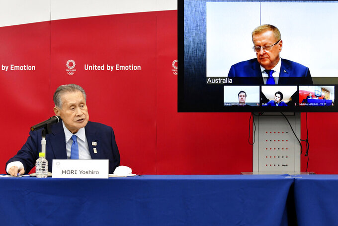 Tokyo 2020 Organizing Committee President Yoshiro Mori, left, speaks in teleconference with John Coates, chairman of the IOC's Coordination Commission for the Tokyo 2020 Olympic Games, in Tokyo Thursday, April 16, 2020. Tokyo Olympic organizers and the IOC said Thursday they will cut some of the extras out of next year's postponed games, an attempt to limit what is expected to be billions of dollars in added expenses.(Kazuhiro Nogi/Pool Photo via AP)