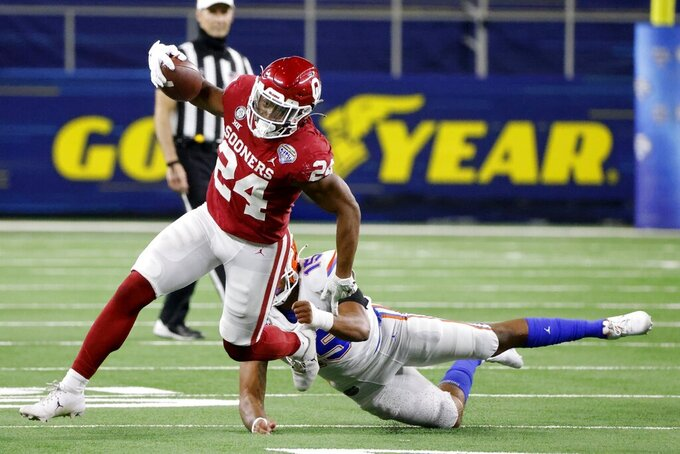 Oklahoma running back Marcus Major (24) breaks a tackle attempt by Florida linebacker Derek Wingo (15) on the way to a touchdown during the second half of the Cotton Bowl NCAA college football game in Arlington, Texas, Wednesday, Dec. 30, 2020. (AP Photo/Michael Ainsworth)