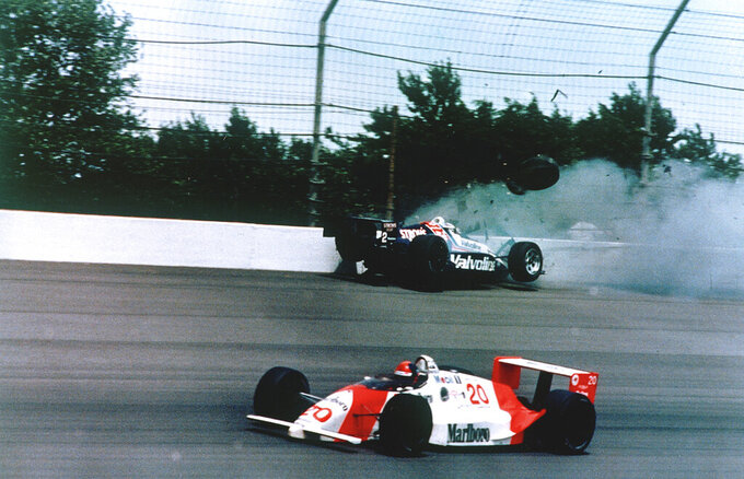 FILE - In this May 28, 1989, file photo, Emerson Fittipaldi, bottom, takes the lead with less than two laps remaining as Al Unser Jr. crashes into the wall during the 73rd running of the Indianapolis 500 auto race at Indianapolis Motor Speedway in Indianapolis, Ind. The Associated Press has updated its survey of living Indianapolis 500 winners and their pick as the greatest race in the long history of the event. There are six races that received multiple votes, topped by Al Unser Jr.'s victory over Scott Goodyear in 1992 — the closest Indy 500 in history. The others are Fittipaldi's win in 1989; Sam Hornish Junior's win in 2006; the 1982 battle between Rick Mears and Gordon Johncock; the 2011 race won by the late Dan Wheldon; and the 2014 thriller won by Ryan Hunter-Reay.(AP Photo/Ron Weaver, File)