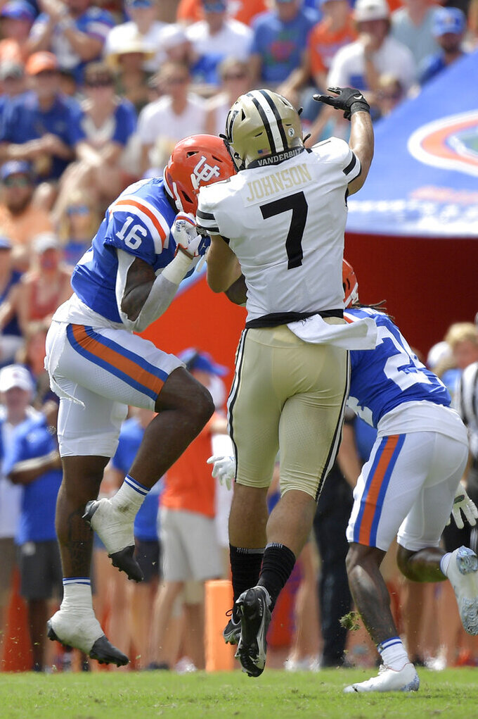 Vanderbilt wide receiver Cam Johnson (7) is hit by Florida safety Tre'Vez Johnson (16) after throwing a pass during the first half of an NCAA college football game, Saturday, Oct. 9, 2021, in Gainesville, Fla. Florida's Johnson received a targeting penalty and was ejected from the game on the play. (AP Photo/Phelan M. Ebenhack)