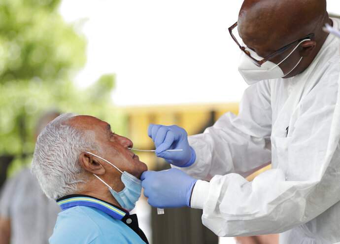 Lab technician James Donald, right, uses a nasal swab to test Hugo Marti for COVID-19, Tuesday, July 28, 2020, at the AHEPA Apartments in Miami. Miami-Dade County Commissioner Esteban