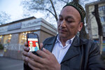 In this March 31, 2018, photo, Omir Bekali holds up a mobile phone showing a photo of his parents whom he believes have been detained in China, in Almaty, Kazakhstan. Since 2016, Chinese authorities in the heavily Muslim region of Xinjiang have ensnared tens, possibly hundreds of thousands of Muslim Chinese, and even foreign citizens, in mass internment camps. The program aims to rewire detainees' thinking and reshape their identities. Chinese officials say ideological changes are needed to fight Islamic extremism.  (AP Photo/Ng Han Guan)