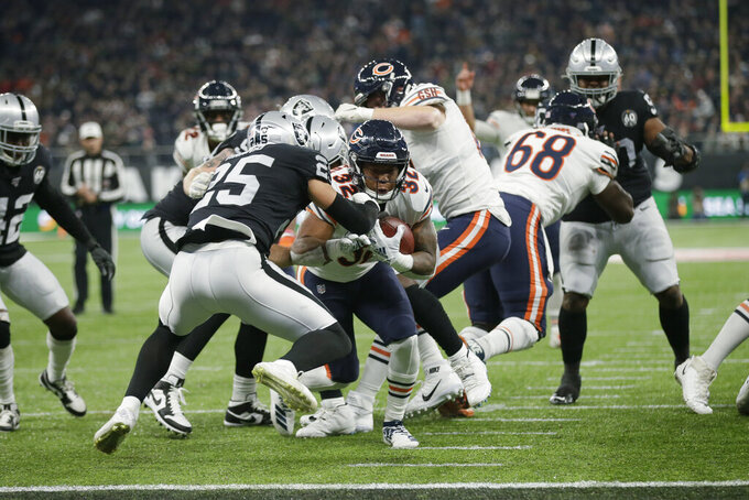 Chicago Bears running back David Montgomery (32) goes in for a touchdown against Oakland Raiders free safety Erik Harris (25) during the second half of an NFL football game at Tottenham Hotspur Stadium, Sunday, Oct. 6, 2019, in London. (AP Photo/Tim Ireland)