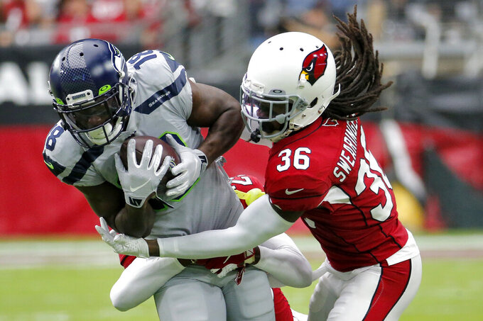 Arizona Cardinals free safety D.J. Swearinger (36) tackles Seattle Seahawks wide receiver Jaron Brown (18) during the first half of an NFL football game, Sunday, Sept. 29, 2019, in Glendale, Ariz. (AP Photo/Rick Scuteri)