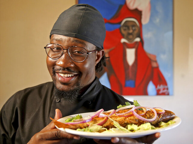 This Oct. 31, 2019 photo shows Ricardo Jean-Baptiste with Whole Fish at Rendez-Vous Creole in New Orleans. Jean-Baptiste wants the city to know about epis, the blend of garlic, peppers and herbs at the foundation of so many Haitian dishes. He wants them to taste conch simmered in Creole sauce, the sharply spicy slaw pikliz, the starchy, smashed plantains called bannan fri and gratine, a mac and cheese he makes with ground beef. (Michael DeMocker/The Daily Advertiser via AP)