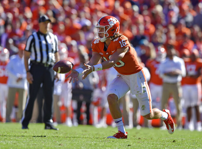 Clemson quarterback Trevor Lawrence tosses a lateral pass during the first half of an NCAA college football game against Louisville, Saturday, Nov. 3, 2018, in Clemson, S.C. (AP Photo/Richard Shiro)