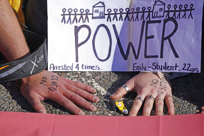A view of the hands of protesters from Insulate Britain stuck to the ground as they block the A20 which provides access to the Port of Dover, in Kent, England, Friday, Sept. 24, 2021. The environmental activists have moved location after been banned from campaigning on the M25 motorway in London. (Gareth Fuller/PA via AP)
