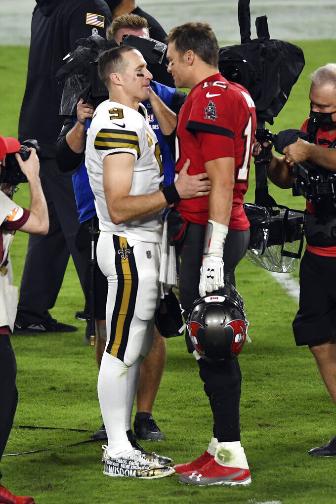 FILE - In this Nov. 8, 2020, file photo Tampa Bay Buccaneers quarterback Tom Brady (12) congratulates New Orleans Saints quarterback Drew Brees (9) after an NFL football game in Tampa, Fla. Brees, the NFL's leader in career completions and yards passing, has decided to retire after 20 NFL seasons, including his last 15 with New Orleans. (AP Photo/Jason Behnken, File)