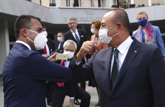 Turkey's Foreign Minister Mevlut Cavusoglu, right, and Italy's Foreign Minister Luigi Di Maio say goodbye by using their elbows after their joint press conference, in Ankara, Turkey, Friday, June 19, 2020.(Fatih Aktas/Turkish Foreign Ministry via AP, Pool)