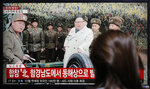 A woman watches a news program reporting North Korea's firing unidentified projectiles with a file image of North Korean leader Kim Jong Un, in Seoul, South Korea, Thursday, Nov. 28, 2019. North Korea on Thursday fired an unidentified projectile, South Korea's military said, three days after the North said its troops conducted artillery drills near its disputed sea boundary with South Korea. (AP Photo/Lee Jin-man)