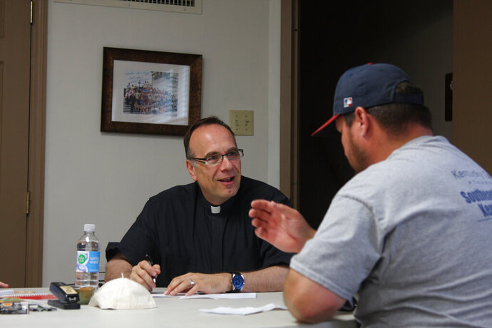 Father Jim Sichko, left, a Lexington priest, pays the electric bill of an out-of-work coal miner at Holy Trinity Catholic Church in Harlan, Kentucky, on Monday, July 15, 2019. Sichko handed out more than $20,000 on Monday to miners who are struggling to pay bills after the coal company they work for filed for bankruptcy protection. (Will Wright/Lexington Herald-Leader via AP)
