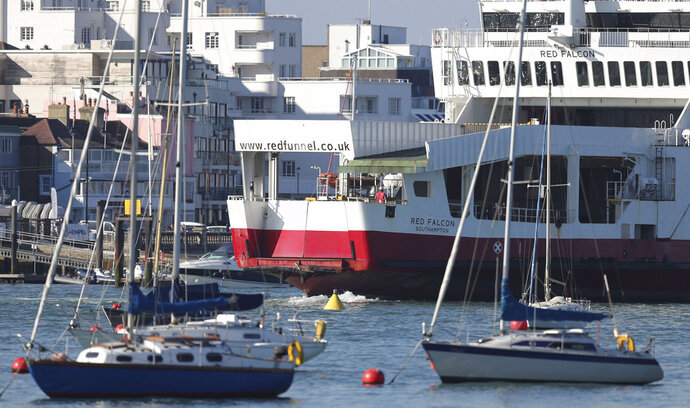 The Red Funnel car ferry, Red Falcon, which earlier collided with several small boats due to bad weather, leaves East Cowes on the Isle of Wight bound for Southampton, southern England, Sunday Oct. 21, 2018.  The ferry collided with several yachts and ran aground while trying to berth at a harbor on the Isle of Wight off southern England in dense fog early Sunday. No injuries were reported. (Andrew Matthews/PA via AP)