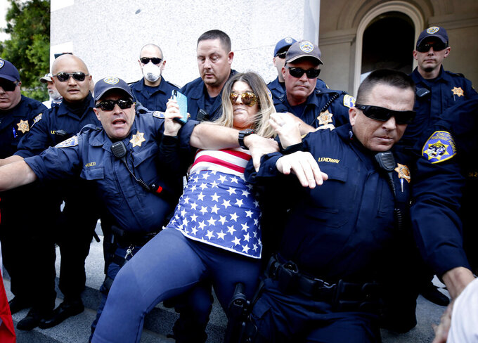 FILE - In this May 1, 2020, file photo, a protester is detained by California Highway Patrol officers during a demonstration against Gov. Gavin Newsom's stay-at-home orders due to the coronavirus pandemic, at the Capitol in Sacramento, Calif.  When President Trump-supporting insurrectionists stormed the U.S. Capitol in an attempt to overturn the presidential election on Wednesday, Jan. 6 2021 the nation was shocked, but not unwarned. A series of dress rehearsals of sorts have played out in statehouses in Michigan, Oregon, Idaho and elsewhere in recent months, with armed protesters forcing their way into buildings. (AP Photo/Rich Pedroncelli, File)