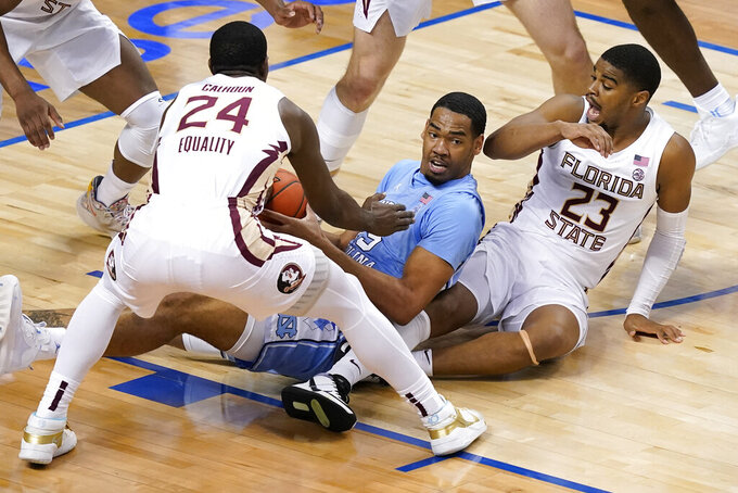 North Carolina forward Garrison Brooks, center, looks for help as Florida State guard Sardaar Calhoun (24) and teammate guard M.J. Walker (23) apply pressure during the first half of an NCAA college basketball game in the semifinal round of the Atlantic Coast Conference tournament in Greensboro, N.C., Friday, March 12, 2021. (AP Photo/Gerry Broome)