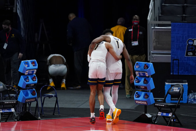 West Virginia's Emmitt Matthews Jr. (11) and Derek Culver (1) hug as they leave the court following a second-round game against West Virginia in the NCAA men's college basketball tournament at Bankers Life Fieldhouse, Sunday, March 21, 2021, in Indianapolis. Syracuse defeated Syracuse 75-72. (AP Photo/Darron Cummings)